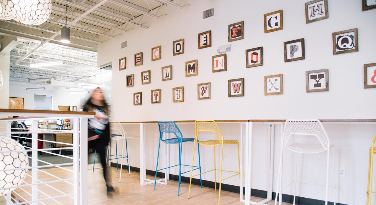 An upstatement employee walks through the office in front of typographic wall art.