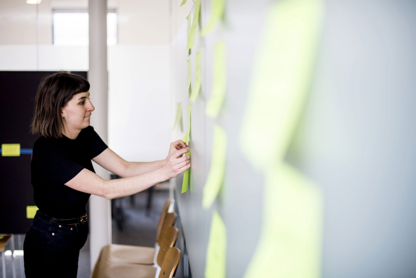Holly arranges post-it notes in a workshop