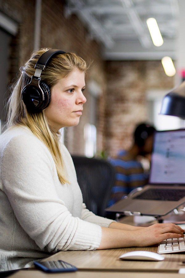 Upstatement employee types at a keyboard with headphones on.