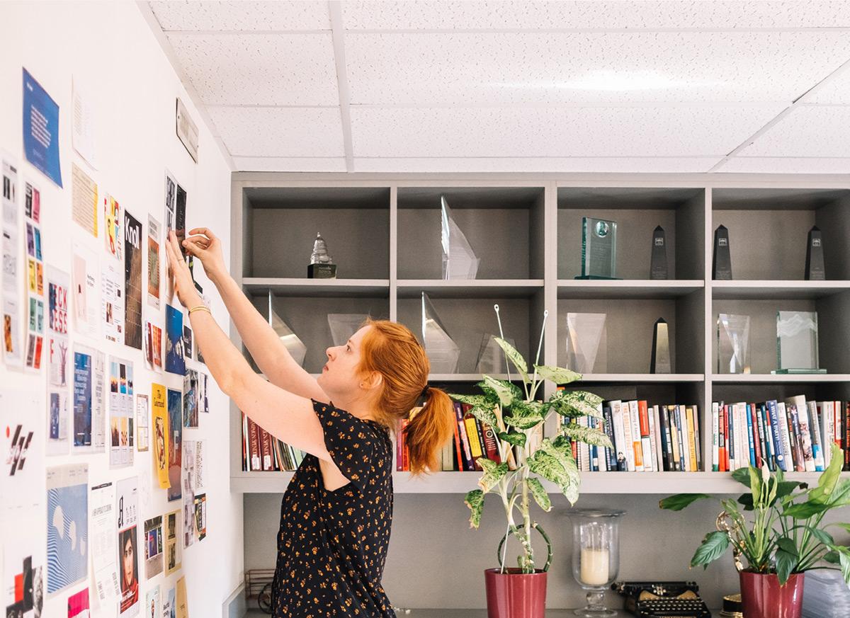 Upstatement employee hangs moodboards on a wall.